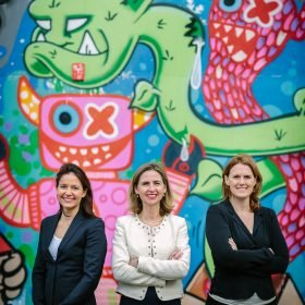 personal branding photo three lady entrepreneurs posing outdoor in front of colourful graffiti brand photo