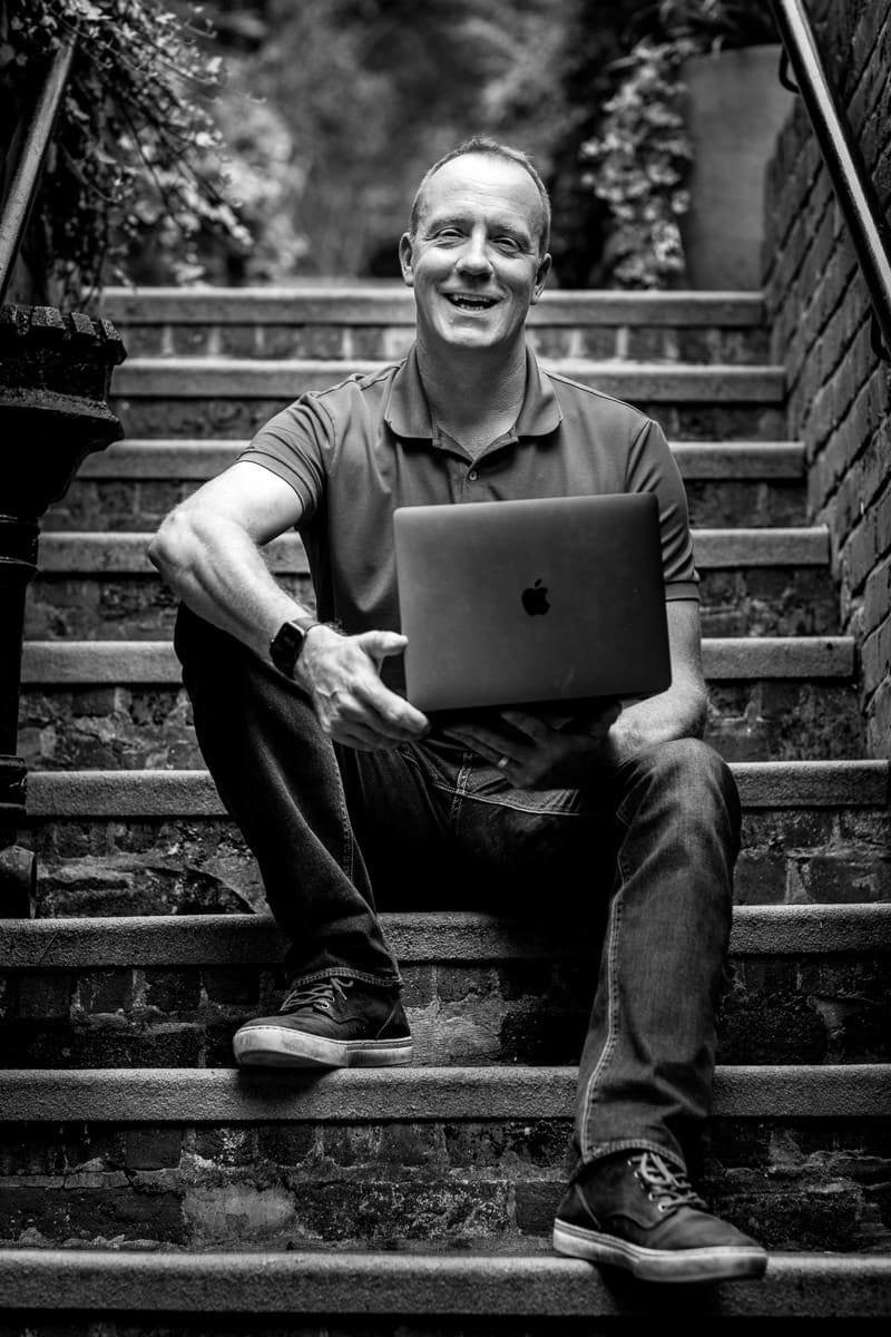 personal branding photo shoot session brand photographer business headshot scott_shanks IT sitting outside outdoor image black_white smiling laptop