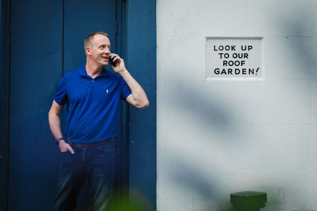 personal branding photo shoot session brand photographer business headshot scott_shanks IT indoor image island_house blue window frame outdoor photo reigate surrey corporate photographer smiling telephone looking up